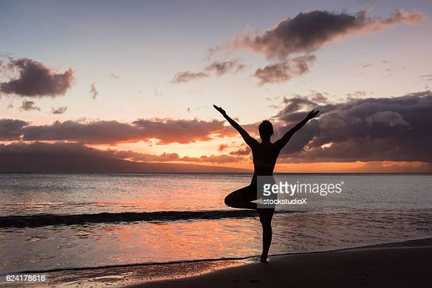 beach yoga at sunset - tree position stock photos and pictures