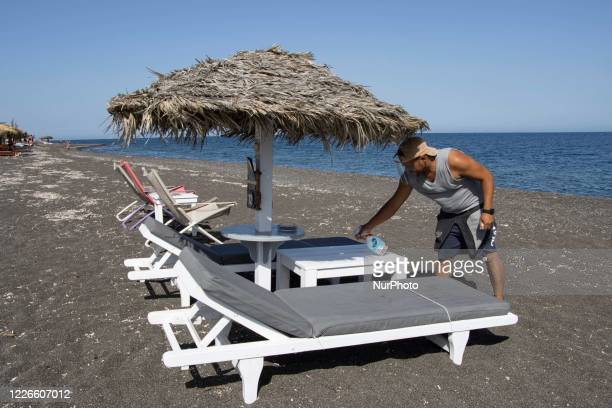 A beachbar employee with face mask and sanitizing cleaning equipment is disinfecting the beach bar umbrella and sunbeds which are kept in a minimum...