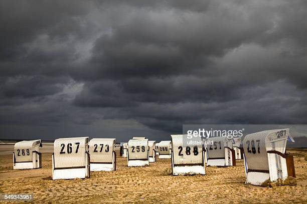 Beachchairs under dark clouds on the island of Spiekeroog one of the East Frisian Islands at the North Sea Coast of Germany