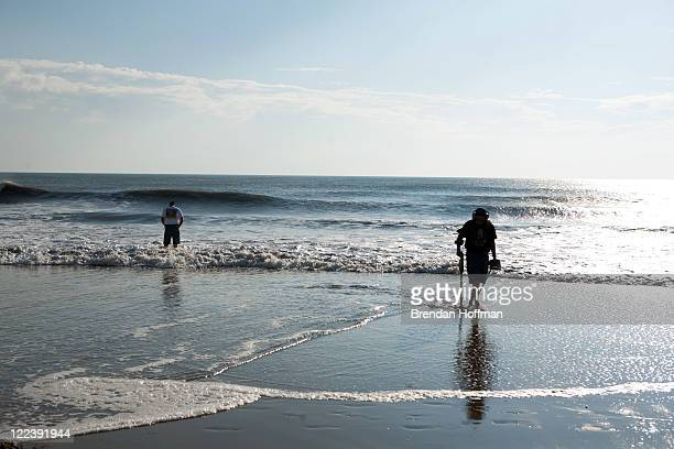 Beachcombers check the surf after Hurricane Irene on August 28 2011 in Virginia Beach Virginia The Category 1 storm which made landfall in North...