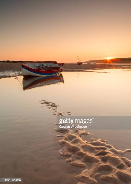 beached boat at sunrise - nautical vessel stock pictures, royalty-free photos & images