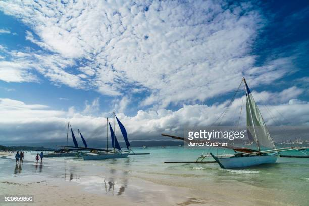 Beached sailboats cast shadows on the long white beach, Borocay Island, Philippines
