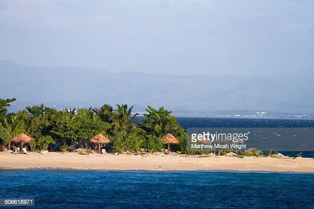 beachfront huts line the island shores - land in sicht stock-fotos und bilder
