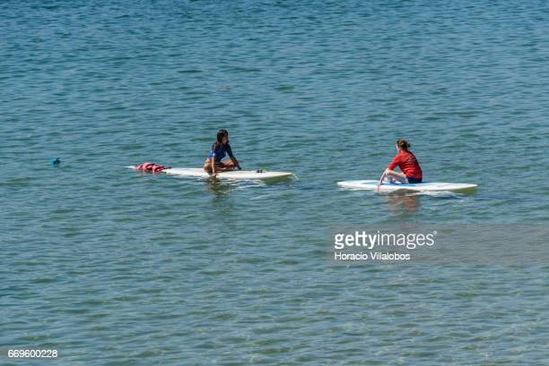 A beachgoer and her instructor sit on paddle boards off Praia da Duquesa on April 16 2017 in Cascais Portugal Although active all year round...