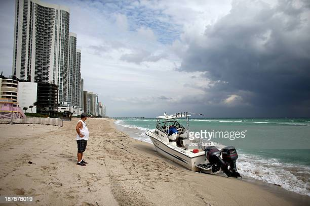 A beachgoer looks at a boat that was found washed ashore on Haulover Beach on November 13 2013 in Haulover Beach Florida The Border Patrol were...