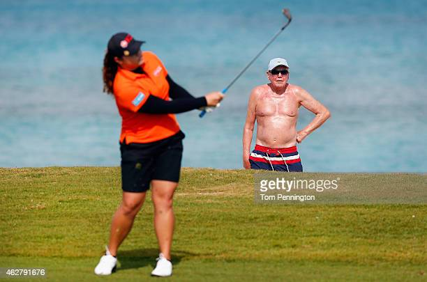A beachgoer looks on as Ariya Jutanugarn of Thailand hits a shot on the eighth hole during round one of the Pure Silk Bahamas LPGA Classic at the...