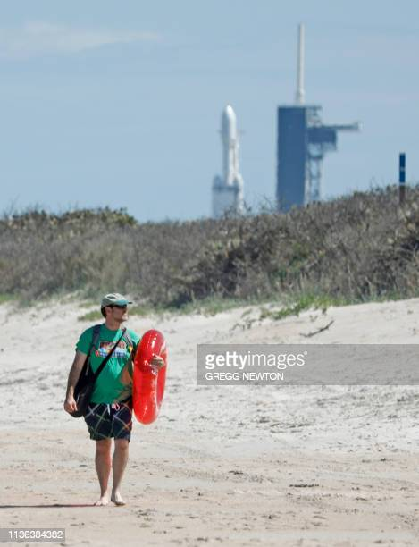 A beachgoer walks a short distance from the SpaceX Falcon Heavy rocket at launch pad 39A near the Kennedy Space Center in Florida on April 11 2019...
