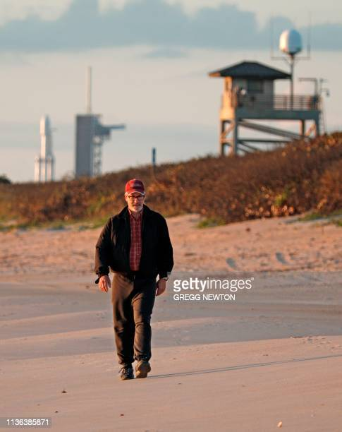 Beachgoer walks a short distance from the SpaceX Falcon Heavy rocket at launch pad 39A near the Kennedy Space Center in Florida, on April 11, 2019. -...