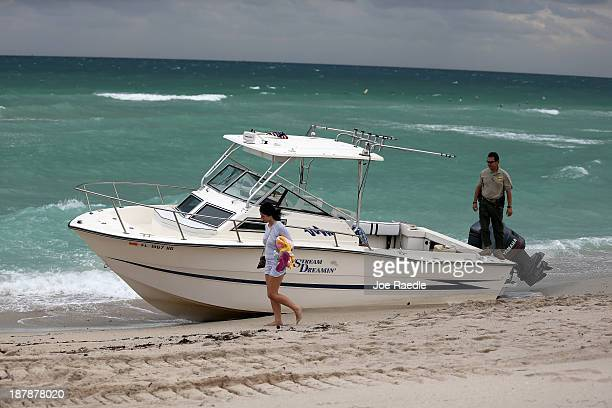 A beachgoer walks past as a Border Patrol agent investigates a boat that was found washed ashore on Haulover Beach on November 13 2013 in Haulover...