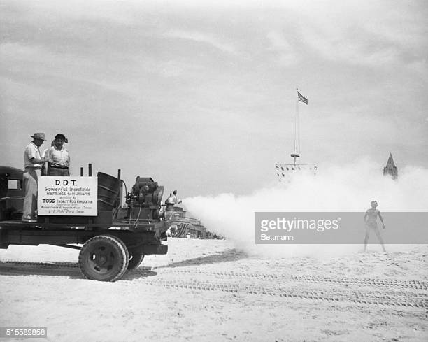 Beachgoers are sprayed with DDT as a new machine for distributing the insecticide is tested for the first time