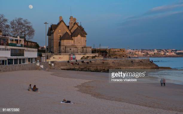 Beachgoers by the sea at sunset under full moon and enjoying mild winter weather at Praia da Duquesa on January 30 2018 in Cascais Portugal Mild and...