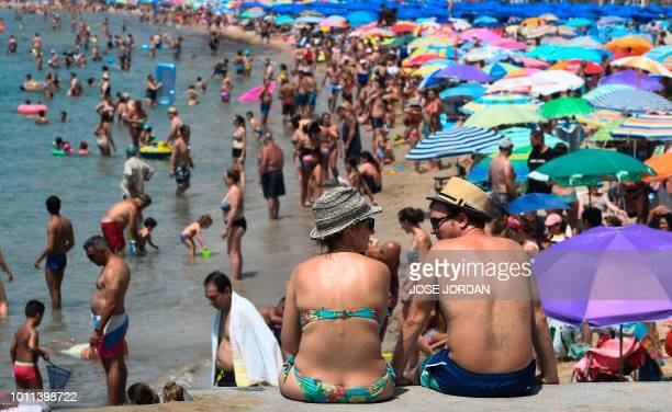 Beachgoers cool off and sunbathe on the beach of the seaside resort of Benidorm on August 5 2018 Europe sweltered through an intense heatwave today...