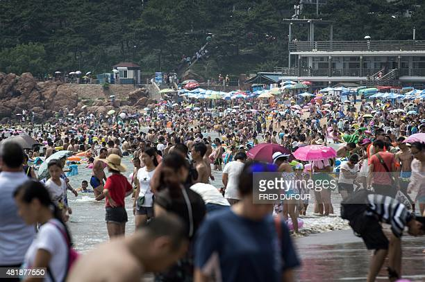 Beachgoers cool themselves by a beach in Qingdao eastern China's Shandong province on July 24 2015 AFP PHOTO / FRED DUFOUR