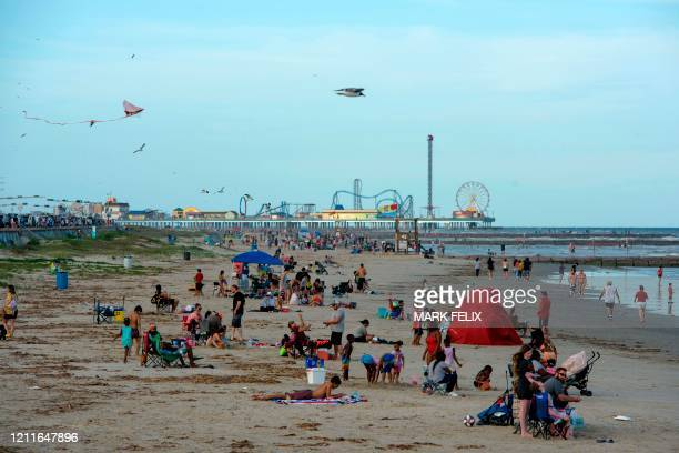 Beachgoers enjoy a day of sunshine at Galveston Beach on May 2 2020 in Galveston Texas amid the coronavirus pandemic Texas beaches were ordered to be...