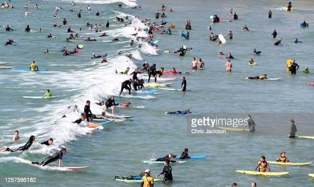 Beachgoers enjoy Polzeath beach on July 21, 2020 in Polzeath, United Kingdom. Many UK residents have decided to go on 'staycations' to Devon and...