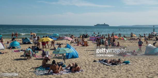Beachgoers enjoy the sun and the good weather at Bournemouth beach ahead of the first significant easing of Britain's lockdown measures during the...