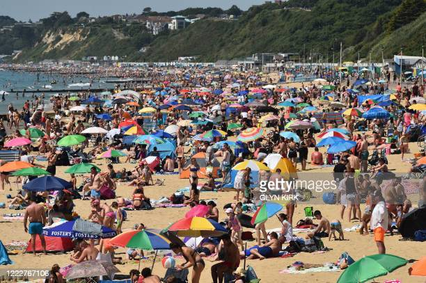 Beachgoers enjoy the sunshine as they sunbathe and play in the sea on Bournemouth beach, southern England, on June 25, 2020. - Just days after...