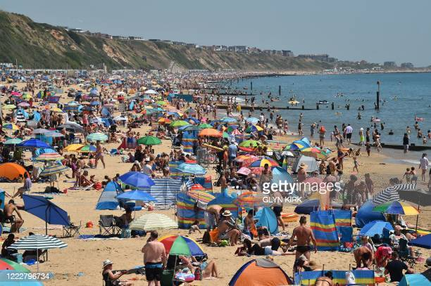 Beachgoers enjoy the sunshine as they sunbathe and play in the sea on Boscombe beach in Bournemouth, southern England, on June 25, 2020. - Just days...