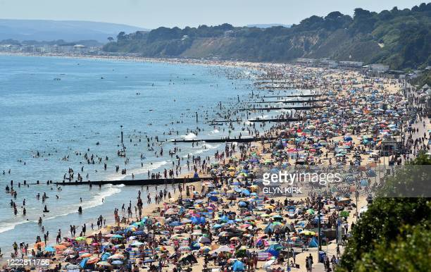 Beachgoers enjoy the sunshine as they sunbathe and play in the sea on Bournemouth beach in Bournemouth southern England on June 25 2020 Just days...