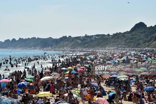 Beachgoers enjoy the sunshine as they sunbathe and play in the sea on Bournemouth beach in Bournemouth, southern England, on June 25, 2020. - Just...