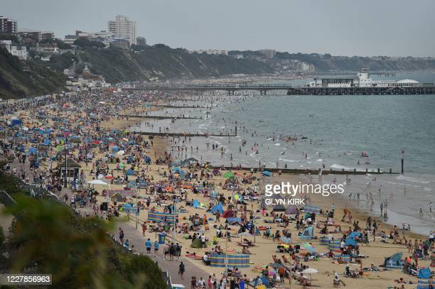 Beachgoers enjoy the sunshine as they sunbathe and play in the sea on Bournemouth beach in Bournemouth, southern England on July 31, 2020 as...