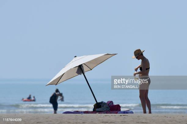 Beachgoers enjoy the sunshine by the sea in Camber Sands southern England on July 25 during a heatwave in Britain
