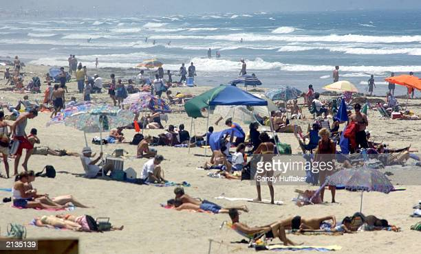 Beachgoers enjoy the weather July 3 2003 at Pacific Beach in San Diego CA Thousands of people are heading to the beaches and parks in anticipation of...