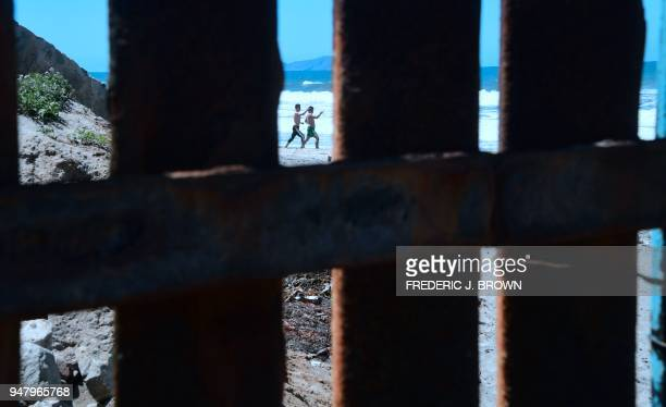 Beachgoers exercise on the beach in La Playa Mexico seen through gaps in the structure separating the US from Mexico which runs for 14 miles inland...
