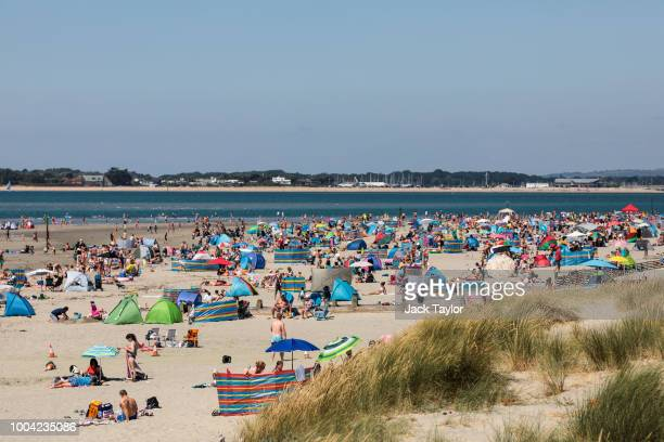 Beachgoers gather on West Wittering Beach during hot weather on the first day of the Summer school holidays on July 23 2018 in Chichester England...