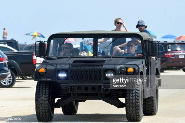 Beachgoers in a humvee ride over a parking lot near the beach at Chincoteague Island Accomack County Virginia during Labor Day weekend on September 1...