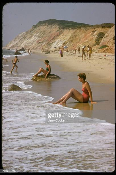 Beachgoers including two women sitting at shore w water lapping up around toes