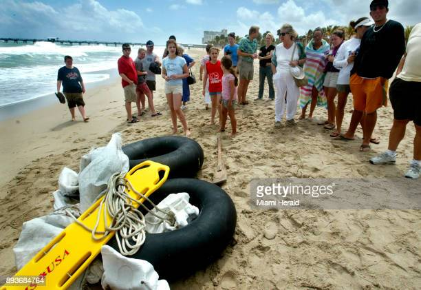 Beachgoers look at inner tubes which were part of a raft that carried Cuban rafters to shore at Lauderdale by the Sea Fla on March 25 2004 The US...