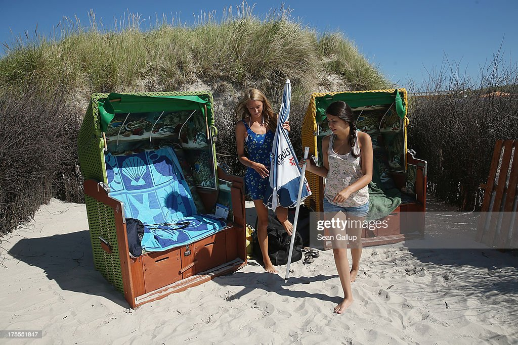 Beachgoers Mia (L) and Martha prepare an umbrella against the sun next to beach basket chairs in hot weather on a sunny day on the south beach of Duene Island on August 4, 2013 near Helgoland, Germany. Duene Island was once an extension of neighboring Heligoland Island until a storm in 1721 severed the connection. Heligoland Island, in German called Helgoland, lies in the North Sea and until World War II was a popular tourist destination. During the war it became strategically vital and all overground structures were obliterated by massive Allied bombing. Today the island has a population of about 1,200 and is again a popular tourist destination known for its abundant wildlife.