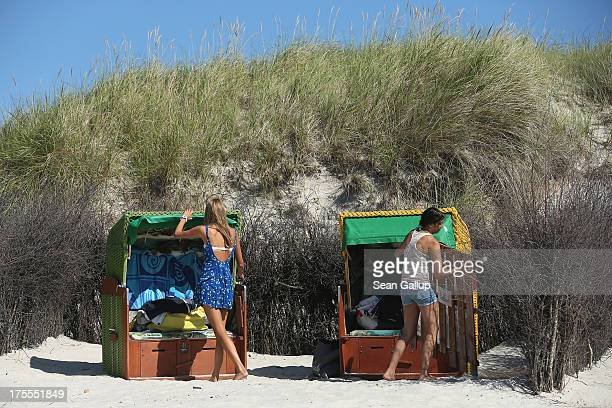 Beachgoers Mia and Martha prepare beach basket chairs in hot weather on a sunny day on the south beach of Duene Island on August 4 2013 near...