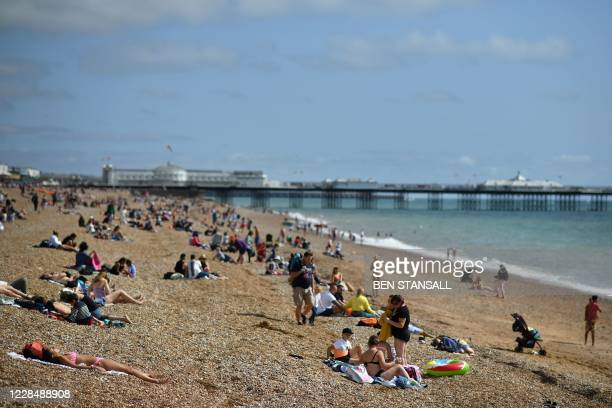 Beachgoers pack the beach in Brighton in the late summer sunshine on the south coast of England on September 13 the day before the UK government...