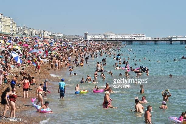 Beachgoers pack the beach in Brighton on the south coast of England as the temperature is expected to hit 37C on August 7 the second day of the...