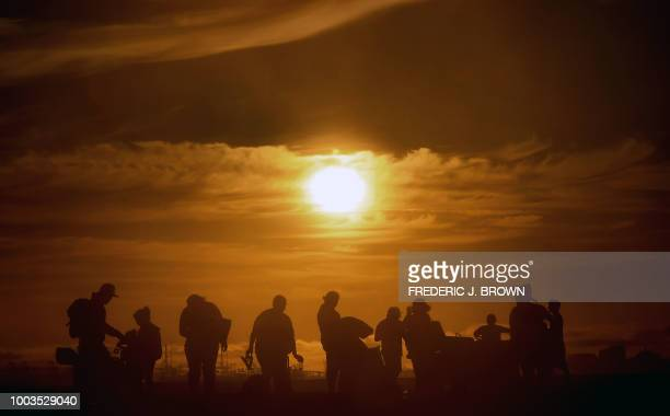 Beachgoers pack their belongings near the end of day at Sunset Beach in Huntington Beach California on July 21 2018 An Excessive Heat Warning for the...