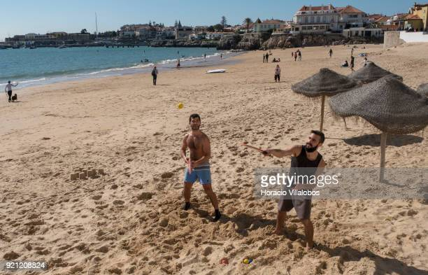 Beachgoers practice Paddle tennis during mild winter weather at Praia da Duquesa on February 18 2018 in Cascais Portugal Mild and sunny winter...