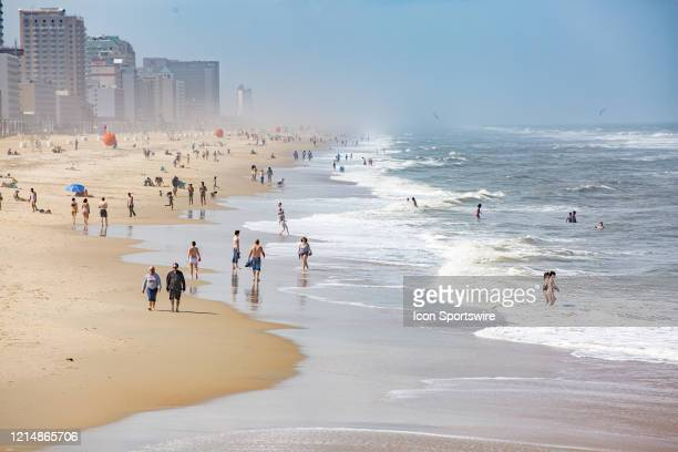 Beachgoers practice social distancing while enjoying Memorial Day weekend on May 22 in Virginia Beach VA This is the first day of the beach's...