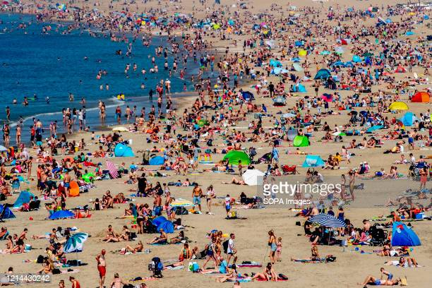 Beachgoers relax and enjoy the sun at Scheveningen beach on the Ascension Day. Warm weather drew crowds to the beach on the Ascension Day despite...