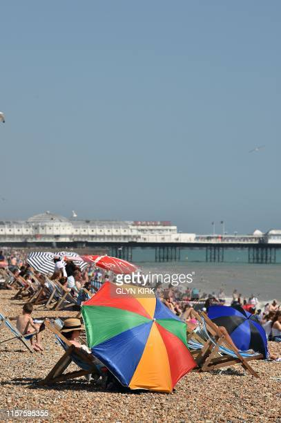 Beachgoers relax by the sea in Brighton southern England on July 24 2019 during a heatwave in Britain Temperatures soared above 30C in Britain on...