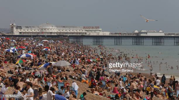 Beachgoers relax on a packed Brighton Beach on July 25 2019 in Brighton United Kingdom The Met Office issued a weather warning from 3pm this...