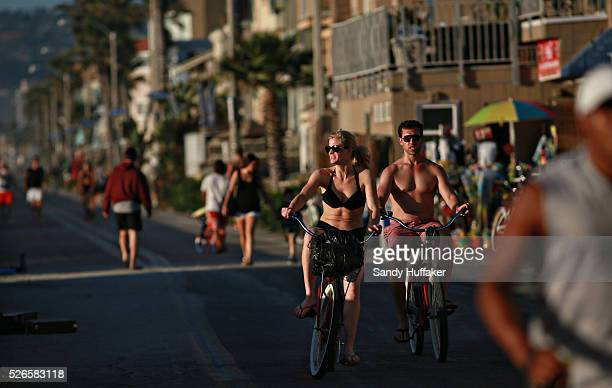 Beachgoers ride bikes along the boardwalk at the beach in Mission Beach in San Diego CA on Monday October 27 2014