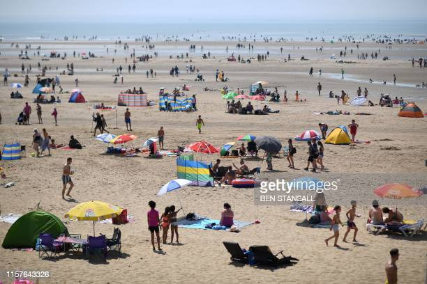 Beachgoers shelter enjoy the sunshine by the sea in Camber Sands southern England on July 25 during a heatwave in Britain