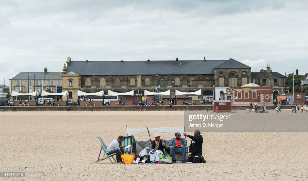 Beachgoers sit on the main beach on August 12, 2017 in Great Yarmouth, England. A cloudy overcast day greeted visitors to the Norfolk seaside town on one of the busiest weekends of the summer period. The town has been a seasiside resort since 1760 and today it has developed renewable energy sources with a wind farm of 30 generators within sight of the town in the North Sea. Thousands of British holidaymakers will visit the area over the summer period.