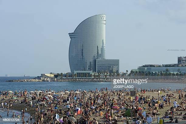Beachgoers sunbathe on a beach of Barcelona with the hotel Vela in background on July 12 2015 AFP PHOTO/ JOSEP LAGO