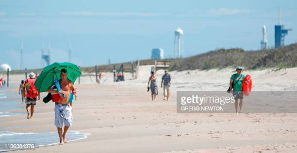Beachgoers walk a short distance from the SpaceX Falcon Heavy rocket at launch pad 39A near the Kennedy Space Center in Florida on April 11 2019 This...