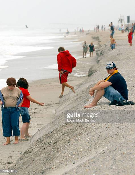 Beachgoers walk on the high and low sides of a berm formed by waves from Hurricane Ophelia on September 11 2005 in Wrightsville Beach North Carolina...