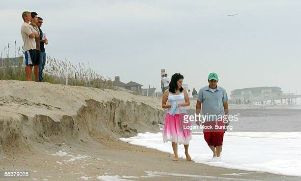 Beachgoers walk on the low side of a berm formed by waves from Hurricane Ophelia on September 11 2005 in Wrightsville Beach North Carolina Hurricane...