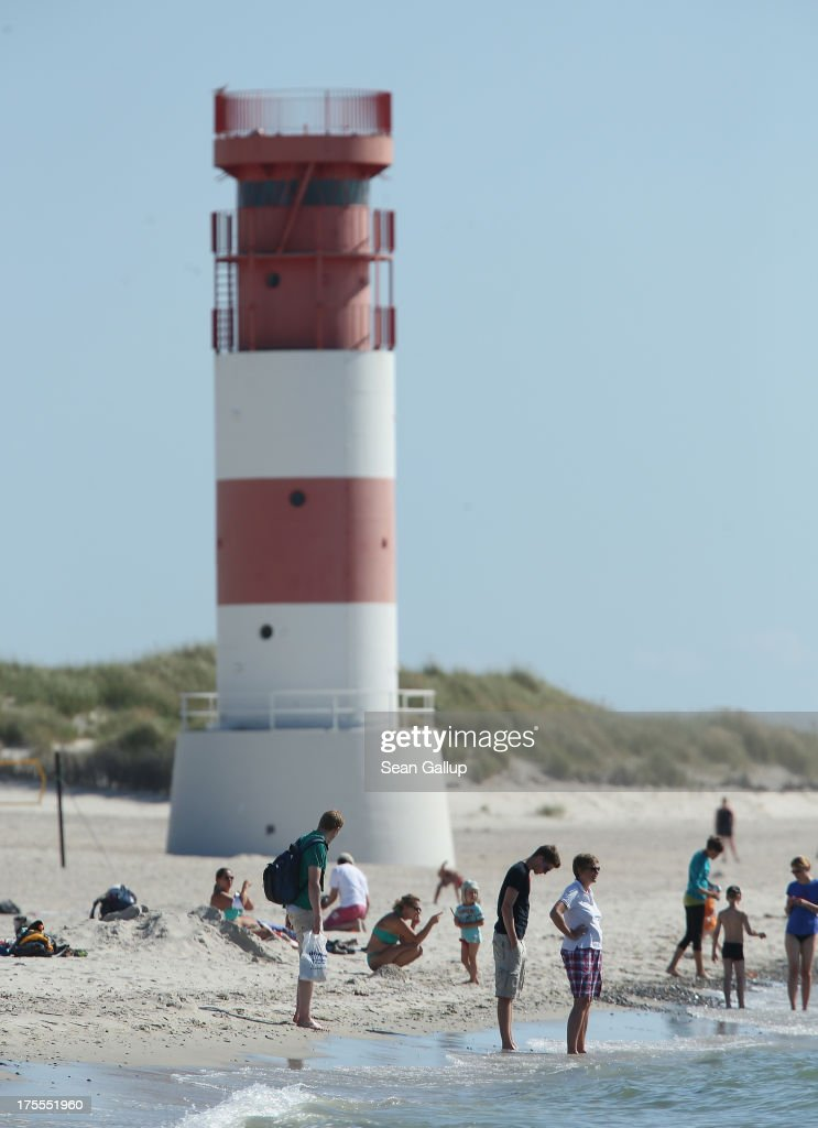 Beachgoers walk on the south beach of Duene Island next to a lighthouse on a hot and sunny day on August 4, 2013 near Helgoland, Germany. Duene Island was once an extension of neighboring Heligoland Island until a storm in 1721 severed the connection. Heligoland Island, in German called Helgoland, lies in the North Sea and until World War II was a popular tourist destination. During the war it became strategically vital and all overground structures were obliterated by massive Allied bombing. Today the island has a population of about 1,200 and is again a popular tourist destination known for its abundant wildlife.